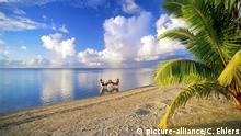 Couple sitting at table sharing afternoon drink in Aitutaki lagoon | Verwendung weltweit
