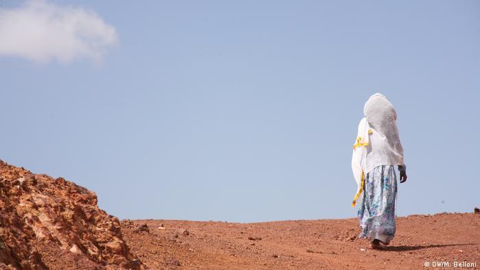 Woman walks through a sandy landscape