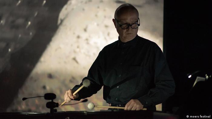 Frank Niehusmann mit Trommelschlägeln vor einer Leinwand (moers festival)