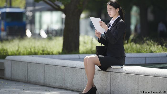 A young businesswoman sits on a bench outside reading papers