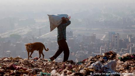 An Indian rag picker carries a sack of sorted recyclable materials at the Ghazipur landfill site in the east of New Delhi