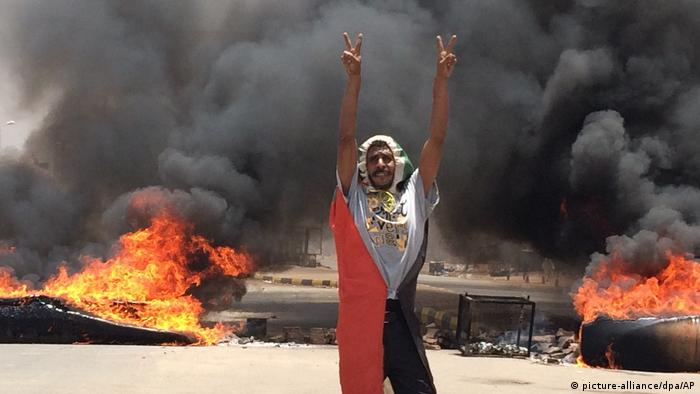 A demonstrator flashes the peace sign while debris burn in the background on June 3, 2019. (AP/dpa photo)