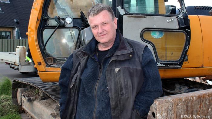 A Danish Hard Line voter standing in front of a digger
