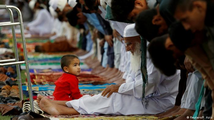 A boy sits with his grandfather who is attending Eid al-Fitr prayers with others to mark the end of the holy fasting month of Ramadan in Peshawar, Pakistan June 4, 2019