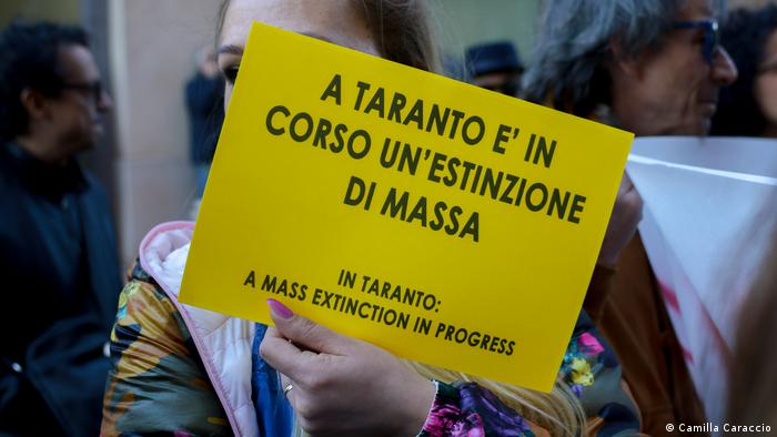A woman holds up a sign reading In Taranto: A mass extinction in progress
