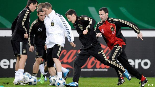 Mesut Oezil, center, runs with the ball during a training session of the German national soccer team in Duesseldorf, Germany, Tuesday, Nov. 17, 2009.