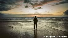 A man stands on the beach watching the waves and sunset over the Pacific Ocean, Oregon, USA, Ocean Shores Oregon USA model released Symbolfoto PUBLICATIONxINxGERxSUIxAUTxONLY Copyright: BrentxOlson OLBR000602