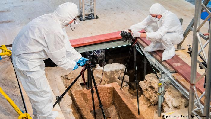 Researchers examine human remains inside a sarcophagus in Mainz, Germany