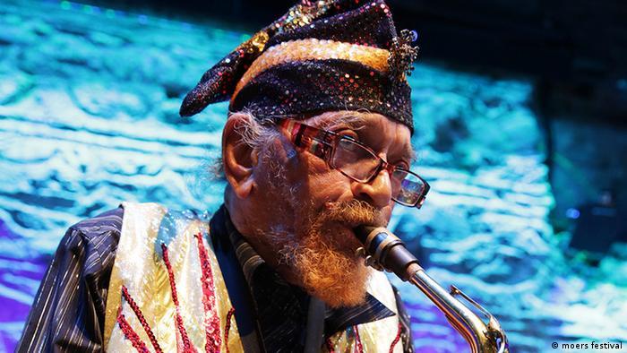 Saxofonist Marshall Allen mit Mütze vor einem bunten Bühnenbild (moers festival)