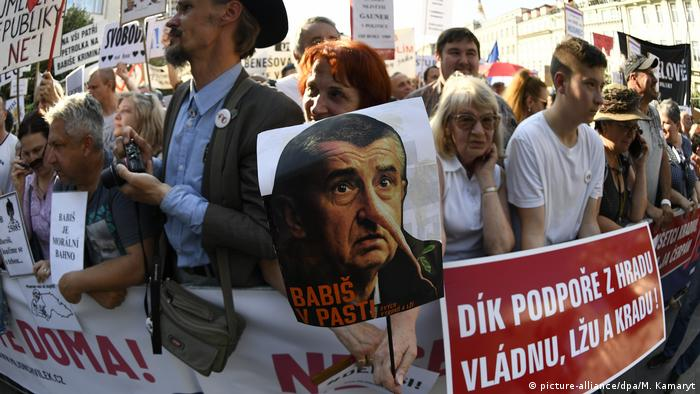 A protester at a rally in Prague holds a poster of Prime Minister Andrej Babis with a long Pinocchio nose (picture-alliance/dpa/M. Kamaryt)