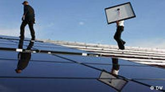 Two men install solar panels on a rooftop