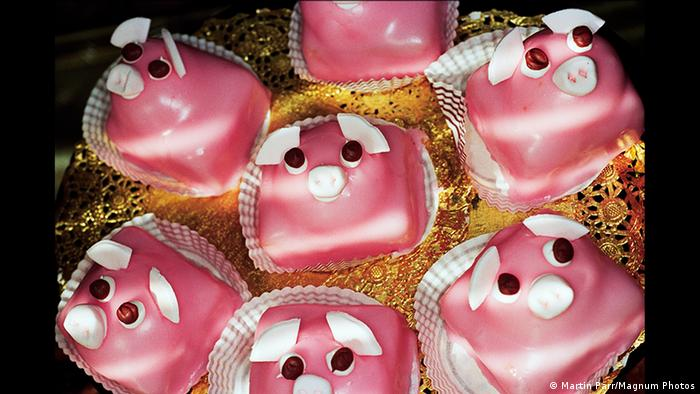 an image of seven pink pig cupcakes arranged on a plate (Martin Parr/Magnum Photos)