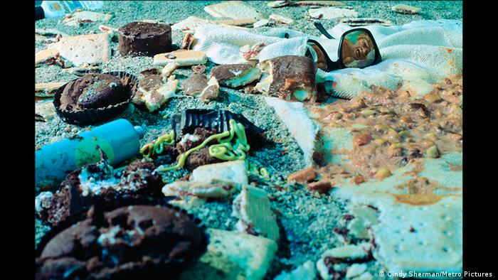 The tormented face of a woman lying on a beach is reflected in sunglasses in the midst of what looks like the rancid remains of a gluttonous beach picnic (Cindy Sherman/Metro Pictures )