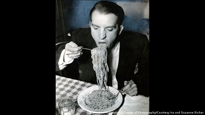 black and white image of a man shoveling a massive fork of pasta into his mouth (Weegee/International Center of Photography/Courtesy Ira und Suzanne Richer)