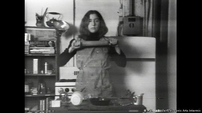 A woman in a kitchen hold up a rolling pin (Martha Rosler/Electronic Arts Intermix)