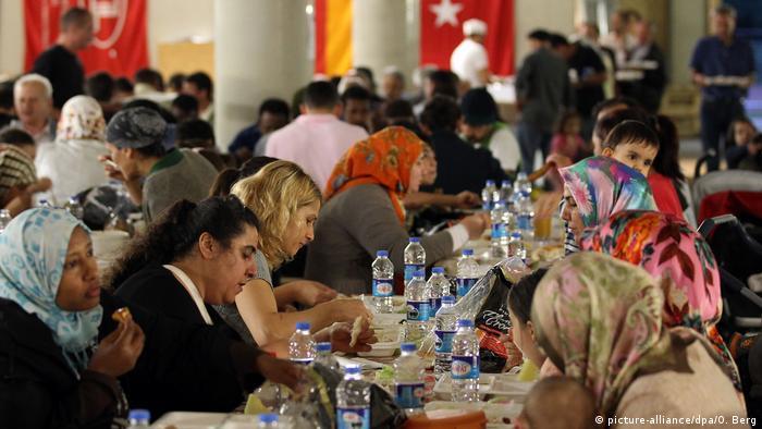 Mulheres, homens e crianças comem juntos