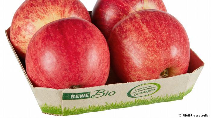 Manzanas en un recipiente de cartón de hierba.
