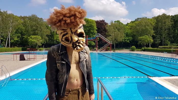 Ein Mitglied der Theatergruppe Helmi steht mit einer Maske vor einem Becken des Sommerbads Humboldthain. (Emir Tebatebai)