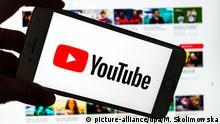 ILLUSTRATION - 26.06.2018, Sachsen, Dresden: Das Logo des Video-Portals YouTube wird auf dem Display eines Smartphones angezeigt. Im Hintergrund ist auf einem Bildschirm die YouTube Homepage zu sehen. Foto: Monika Skolimowska/dpa-Zentralbild/ZB | Verwendung weltweit