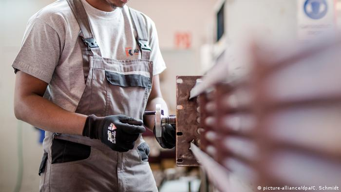 A refugee works in a manufacturing plant (picture-alliance/dpa/C. Schmidt)