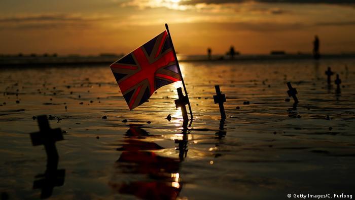 A British flag alongside crosses on Gold Beach, Normandy, France