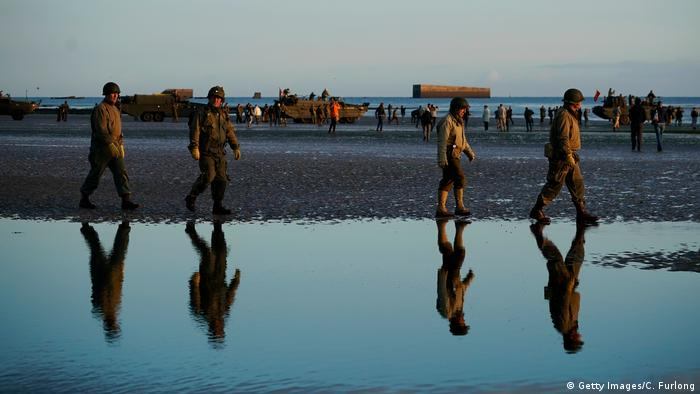 Military reenactors walk along Gold Beach