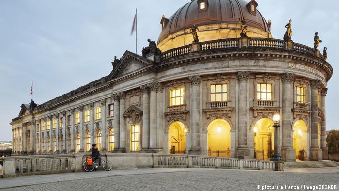 Außenaufnahme des Bode-Museum mit der stuckverzierten Kuppelhalle und den zweiläufigen Treppen in Berlin mit beleuchteten Fenster.
