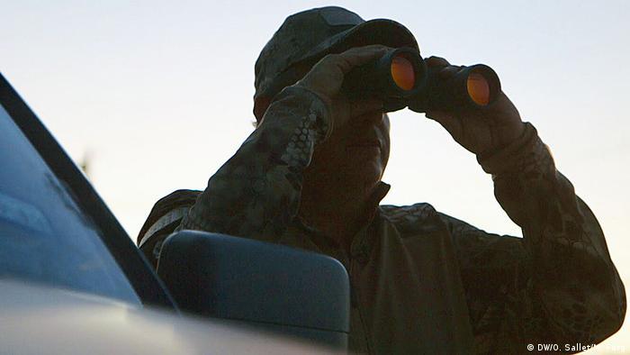 Silhueta de um homem com boné olhando por binóculo