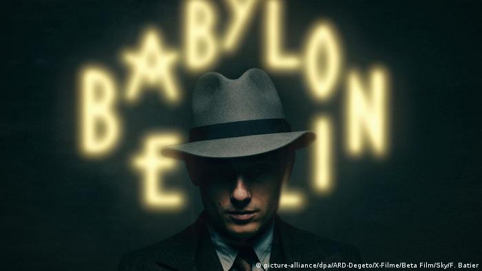 Still from Babylon Berlin shows a man wearing a hat in front of a neon sign (picture-alliance/dpa/ARD-Degeto/X-Filme/Beta Film/Sky/F. Batier)
