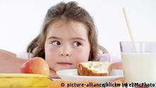 Molliges Mädchen sitzt vor gesundem Frühstück