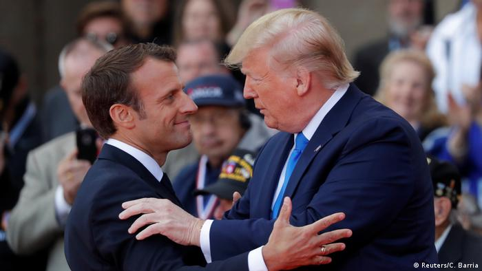 Presidents Macron and Trump greet each other during the D-Day ceremony in Normandy, France