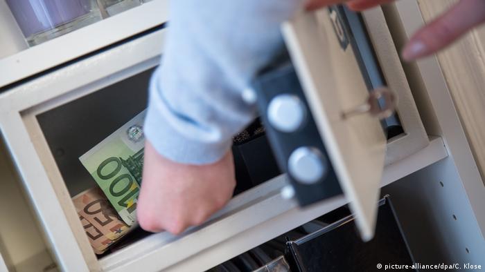 Жена поставя банкноти в сейф