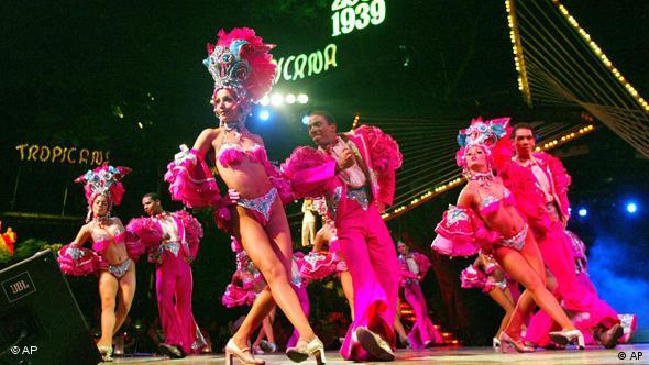 Eine Tanzrevue mit bunt und leicht gekleideten Tänzerinnen und Tänzern. (Foto: AP)