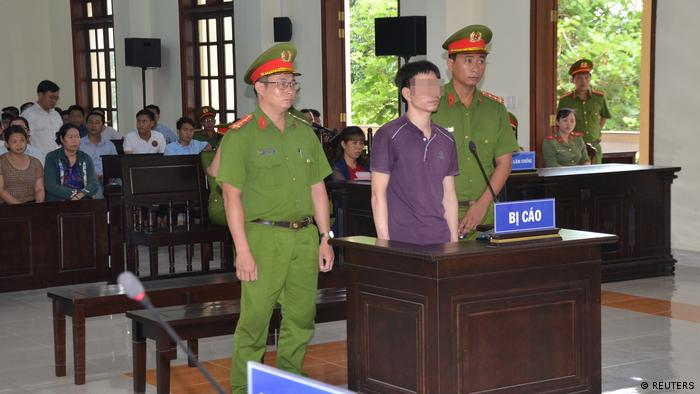 Vietnamese Facebook user Nguyen Ngoc Anh stands between policemen during his trial at a court in Ben Tre province (REUTERS)