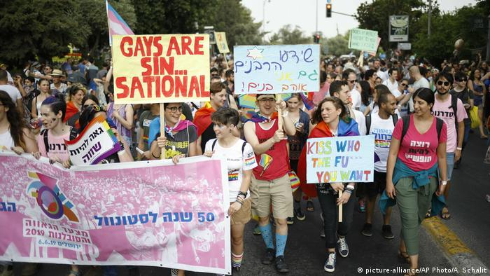 Participants hold signs during the annual Gay Pride parade in Jerusalem,