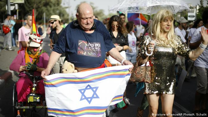 Participants hold flags during the annual Gay Pride parade in Jerusalem,
