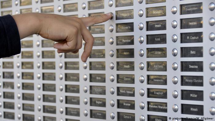 A finger presses a door bell on a large group of bells for an apartment building. (picture-alliance/W. Allgöwer)