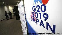 Staffs stand near the emblem of G20 2019 Japan at the entrance of the press center of G20 Finance Ministers' and Central Bank Governors' Meeting Friday, June 7, 2019, in Fukuoka, western Japan. (AP Photo/Eugene Hoshiko)  