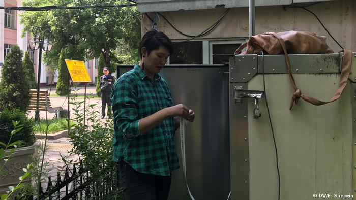 Asya Tulesova changing the filter of an air quality monitoring device in Almaty (DW/E. Sherwin)