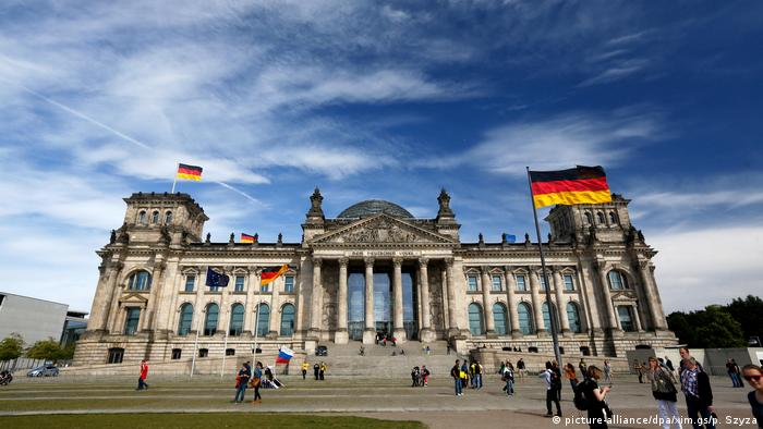 The Reichstag photographed from the front in Berlin with German flags flying in front and atop