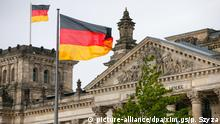 German flags wave in the breeze in front of the parliament building in Berlin