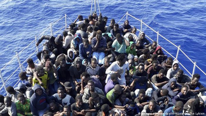 Migrants sitting on a boat of the Libyan coast guard