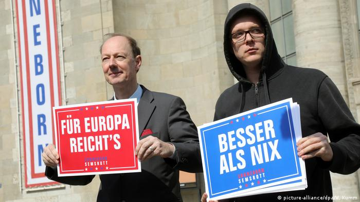 Die Partei reps Martin Sonneborn and Nico Semmsrott hold up placards with campaign slogans