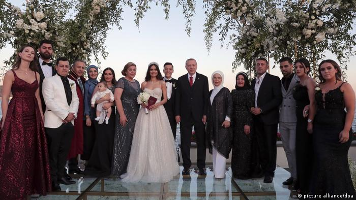 The families of the couple pose for a group photo with Erdogan
