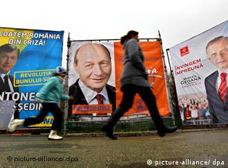 A mother and her son passing the posters of main presidential candidates in Bucharest, Romania, 17 November 2009. Romania will hold its presidential elections on November 22, 2009. From left to right we have the posters belonging to: Crin Antonescu, the leader of National Liberal Party, incumbent president Traian Basescu, and Mircea Geoana, head of Social Democracy Party.