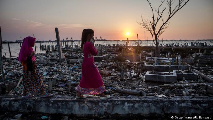 Indonesisches Mädchen während des Sonnenuntergangs an einem Strand