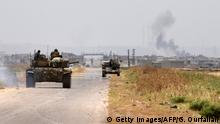 A tank belonging to the Syrian regime forces drives on a road leading to the town of Jalamah in Syria's Hama governorate as smoke billows above buildings during clashes with jihadists on June 8, 2019. - Last week, the jihadists and allied rebels launched a counterattack against regime forces in the northwest of Hama province, seizing two villages amid heavy clashes and airstrikes by regime and Russian forces, according to the Britain-based Syrian Observatory for Human Rights. (Photo by George OURFALIAN / AFP) (Photo credit should read GEORGE OURFALIAN/AFP/Getty Images)
