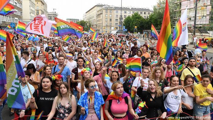 Multidão nas ruas de Varsóvia com bandeiras arco-íris