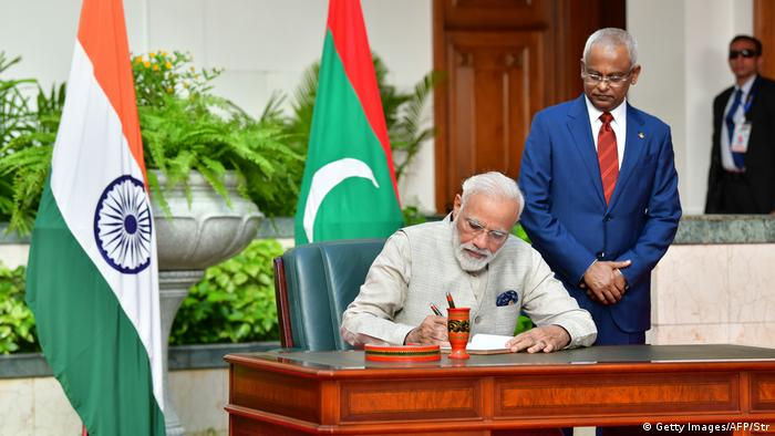 Modi (L) signs documents as Solih looks on during Indian PM's one-day visit to the Maldives