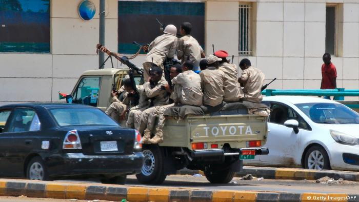 Soldiers sit on the back of a military car (Getty Images/AFP)